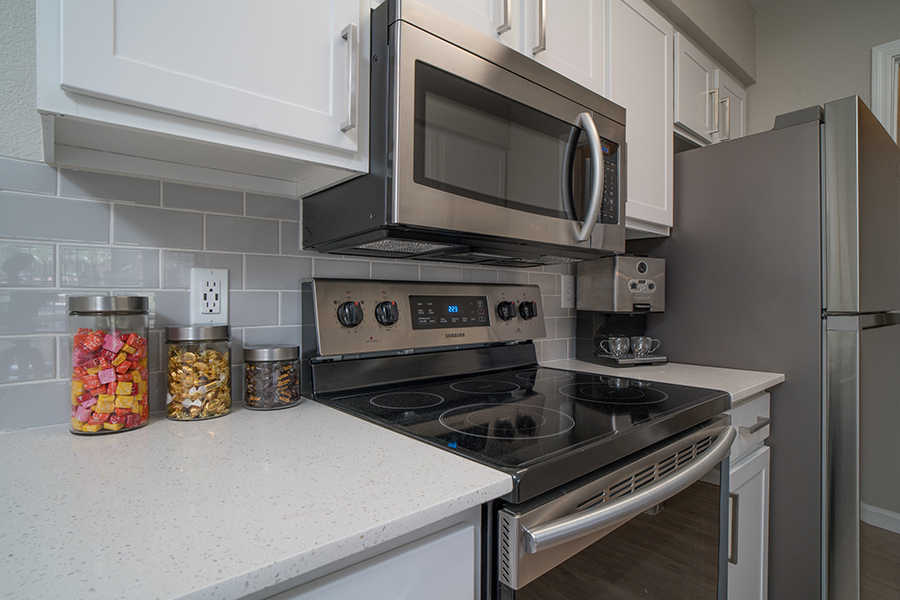 Kitchen with white cabinets and counters, stainless steel appliances, and storage jars with candy.