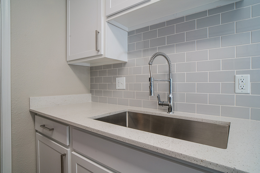 Kitchen with white cabinets and counters, tiled backsplash, and stainless steel sink and faucet.