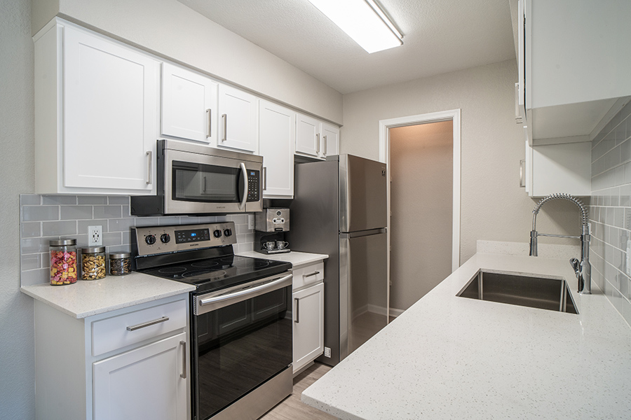 Kitchen with wood floor, white cabinets and counters, and stainless steel appliances.