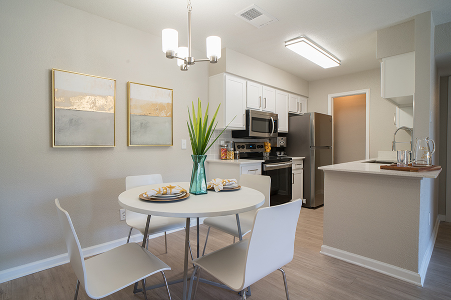 Kitchen and dining room with wood floor, white cabinets, stainless appliances, and modern dining table.