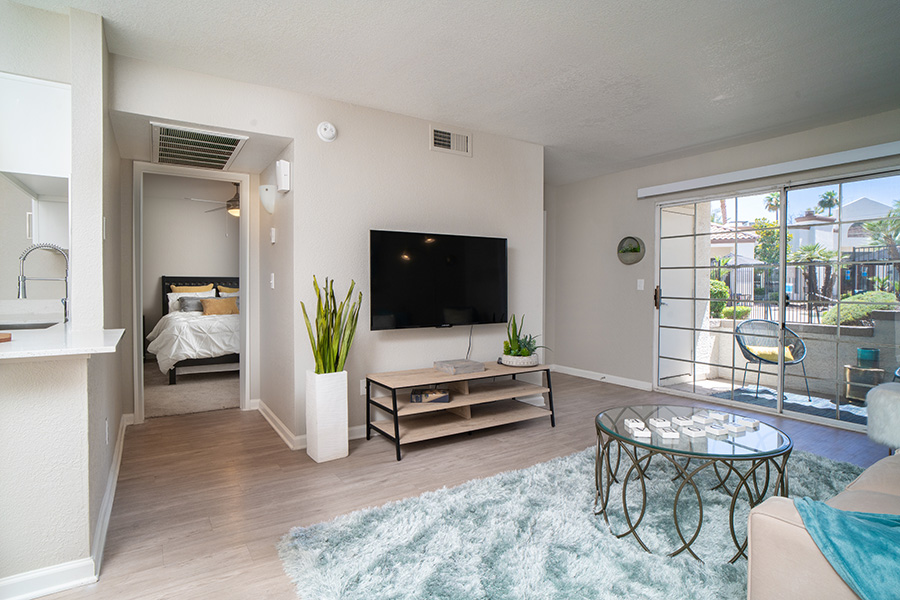 Apartment with wood floor, modern console with wall mounted TV, and doors to balcony and bedroom.