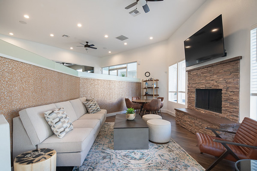 Lounge with plush couch, stone fireplace, wall mounted TV, and comfortable lounge chairs.