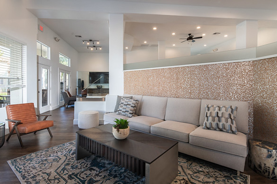 Lounge with large rug, plush couch and lounge chairs, and modern table with succulent plant.