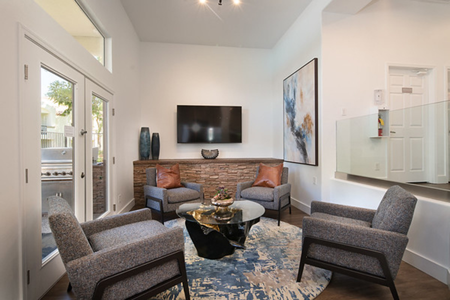 Lounge with large rug, modern coffee table, wall mounted TV, and comfortable modern lounge chairs.