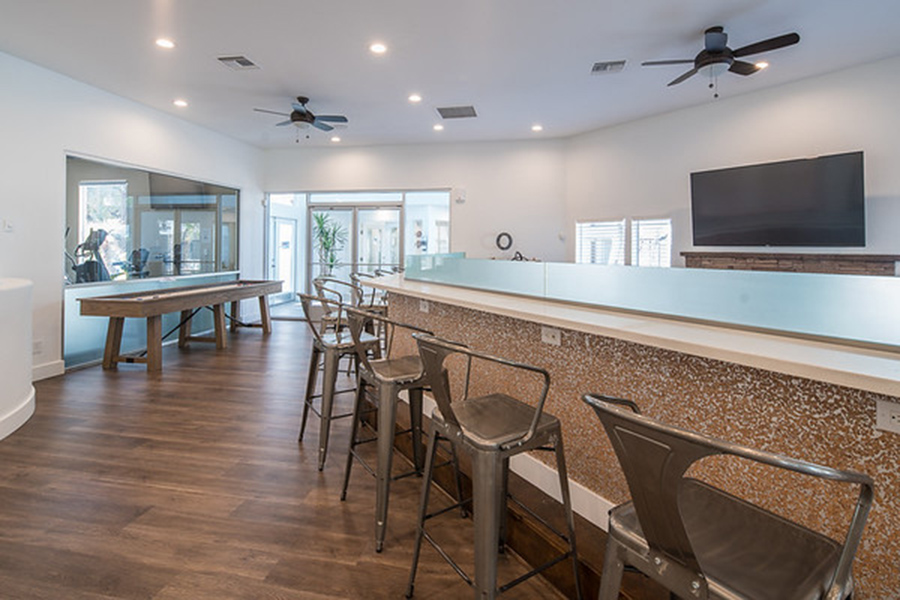 Lounge area with bar, tall metal stools, wall mounted TV, and shuffleboard table.