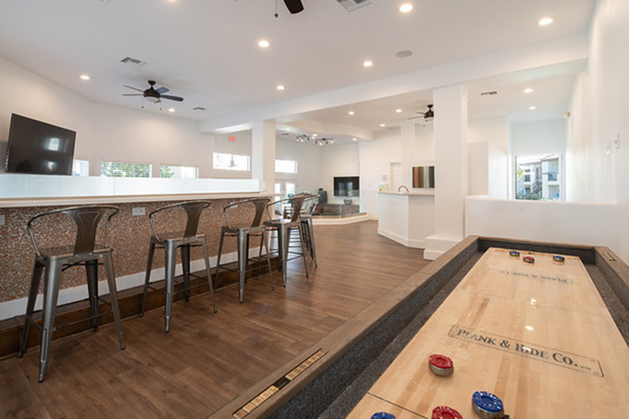 Lounge area with wood floors, tall bar with metal stools, wall mounted TV, and shuffleboard table.
