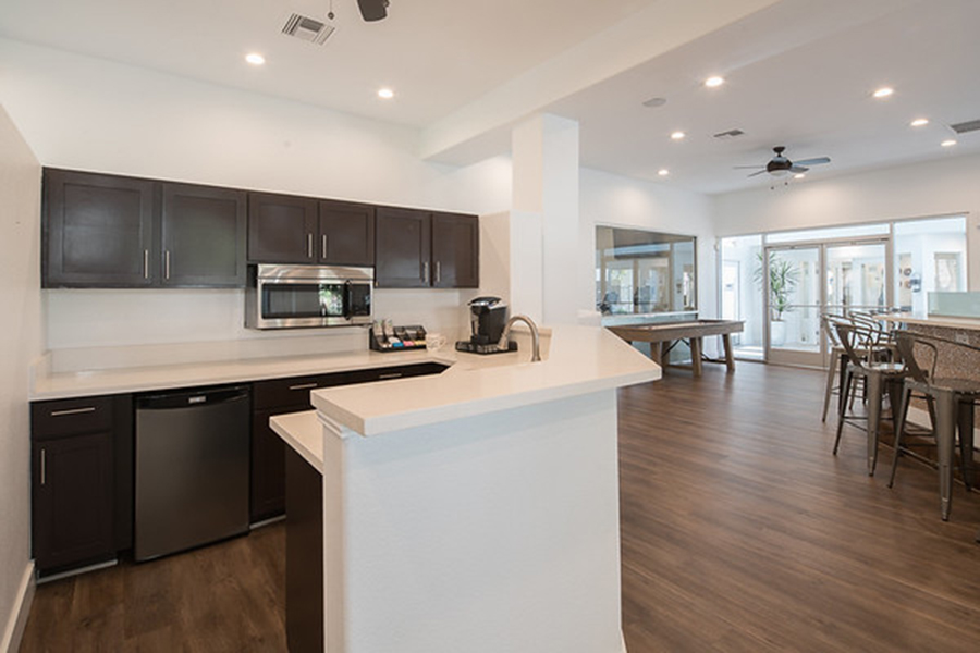 Demo kitchen with wood floors and cabinets, light counters, and stainless steel appliances.