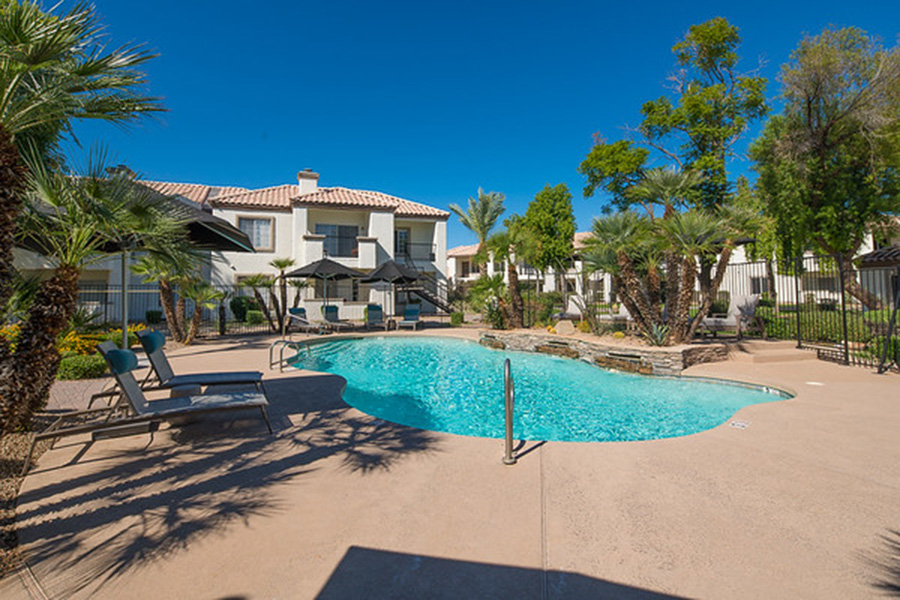 Pool area with lounge chairs, umbrellas, and tall palm trees surrounded by apartments.