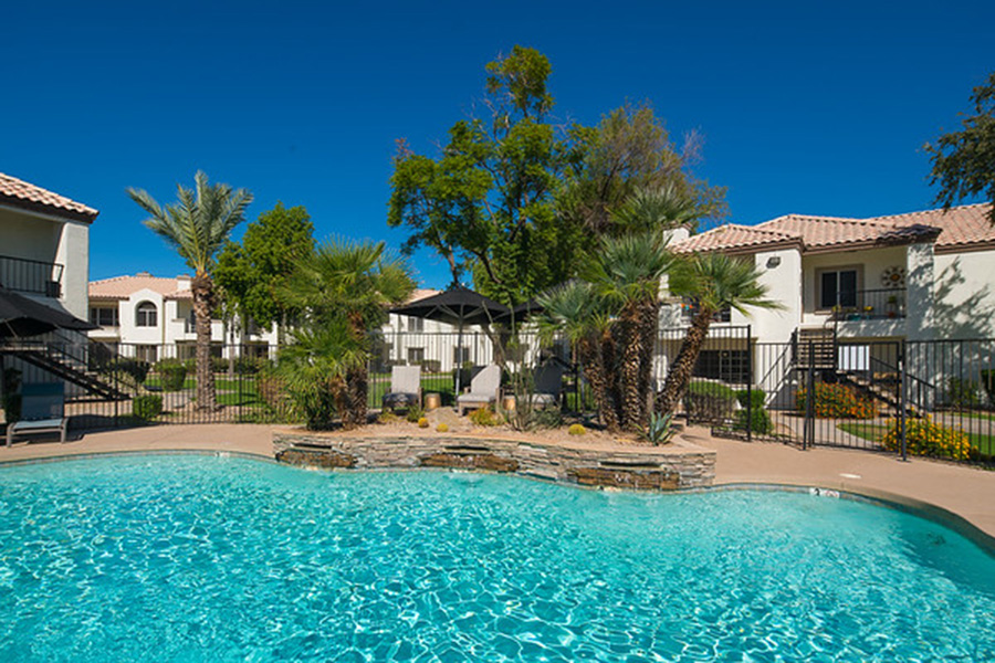 Pool area with blue water, stone walls, lounge chairs, and tall palm trees surrounded by apartments.