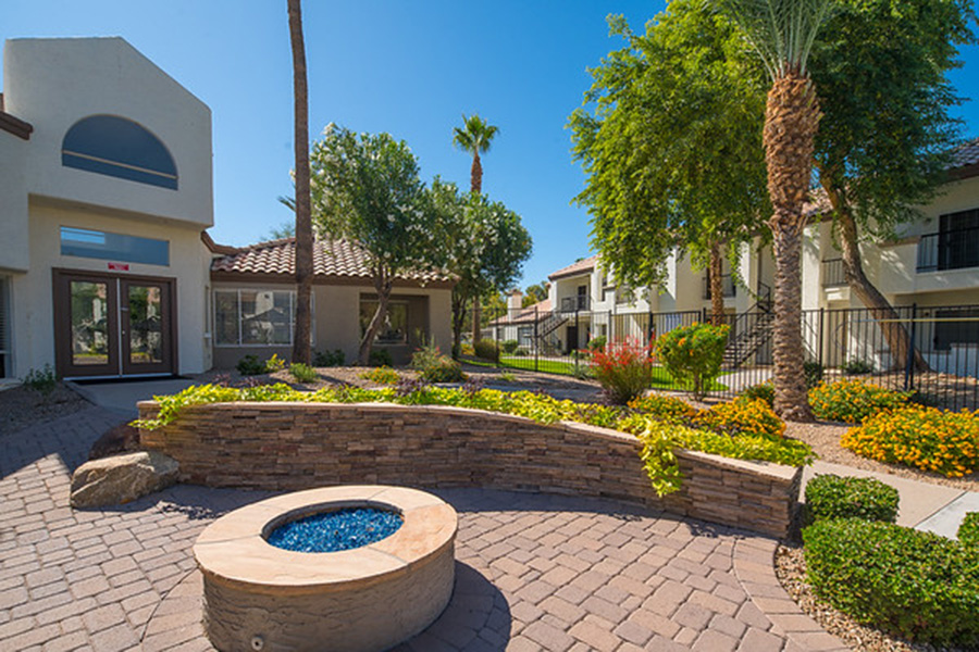 Outdoor lounge with stone pavers, round firepit, stone planters, and tall palm trees.