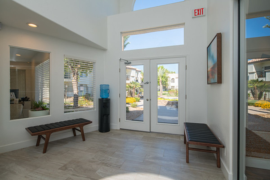 Lobby with large windows, modern bench seats, and water cooler.