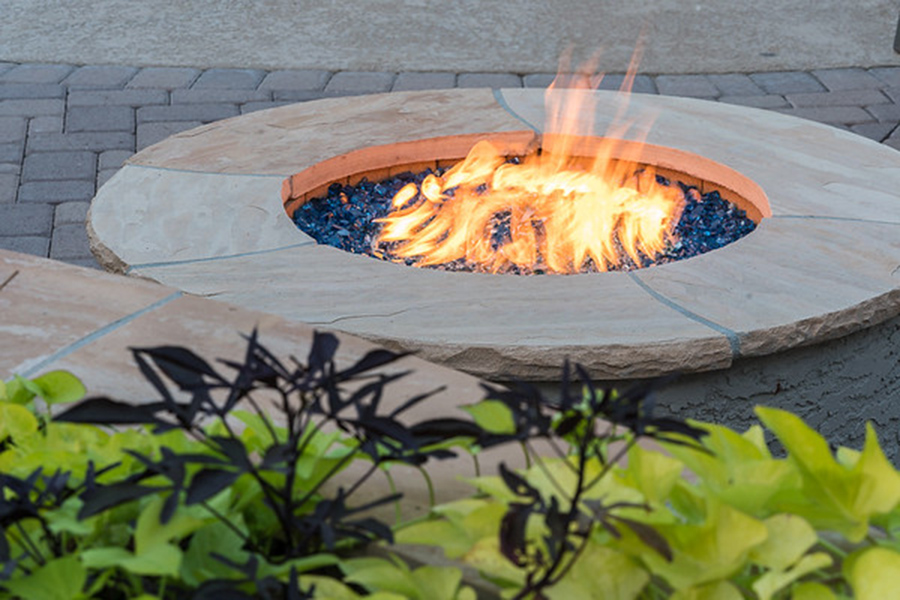 Detail of glowing stone firepit on stone paver patio.