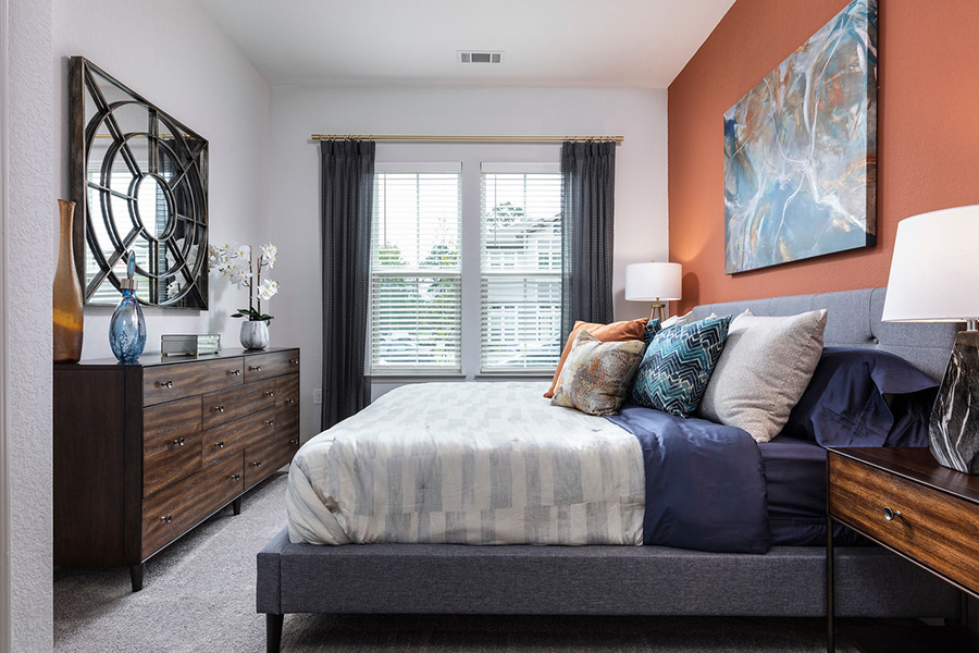 Bedroom with carpet, large plush platform bed with bedding, wood dresser, wall art, and large window.
