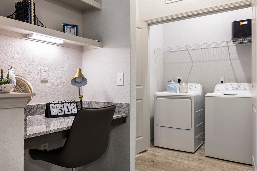 Built in desk and laundry room with shelving and decor.