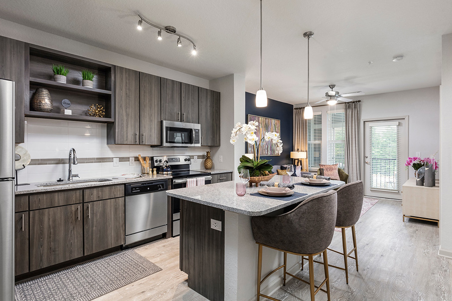 Kitchen with wood style floor and cabinets, stone counter, island with stools, pendant lighting, and stainless steel appliances.