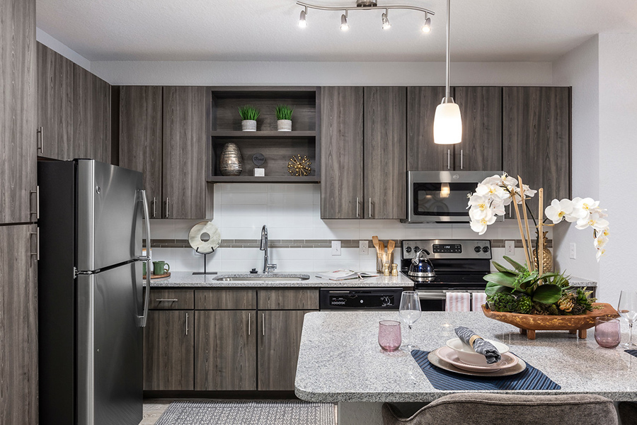 Kitchen with wood cabinets, stone counters, stainless steel appliances, and island with decor.