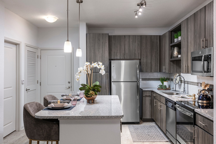 Kitchen with wood cabinets, stone counters, stainless steel appliances, and island with stools and decor.