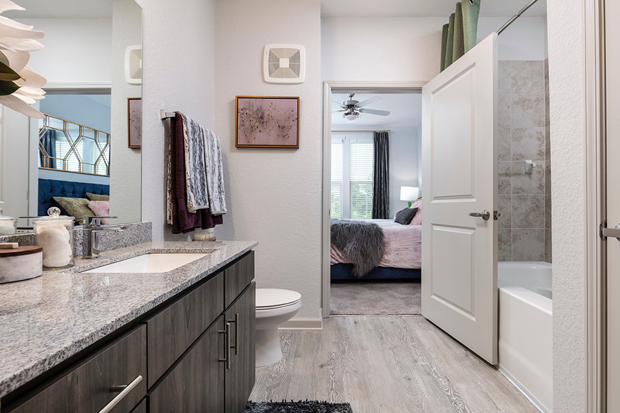 Bathroom with wood style floor and cabinets, stone counter, large mirror, and tiled shower tub with curtain.