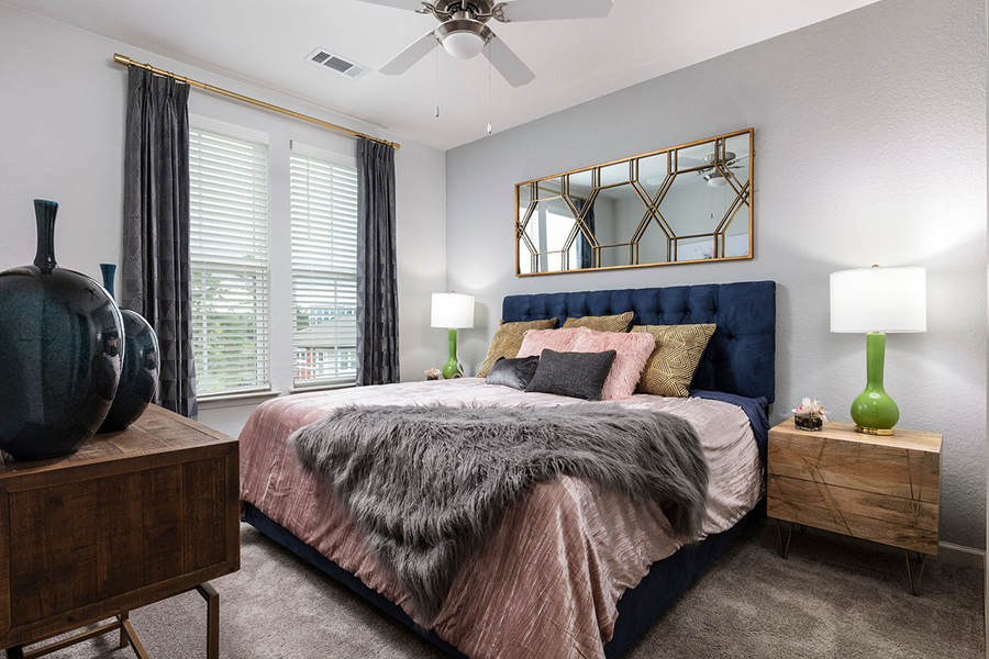 Bedroom with carpet, large platform bed, modern wood furniture, and large window.