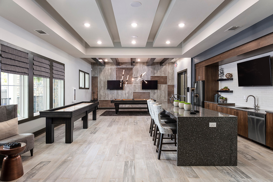 Lounge with tile floor, stone island with stools, stainless steel appliances, and gaming tables.