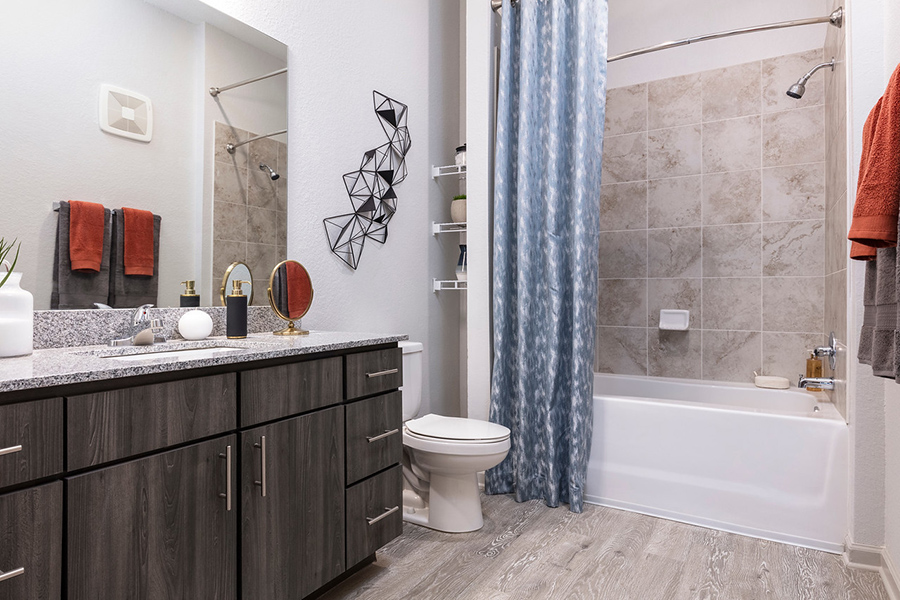 Bathroom with wood style floor, wood cabinets, stone counter, large mirror, and tiled shower tub with curtain.