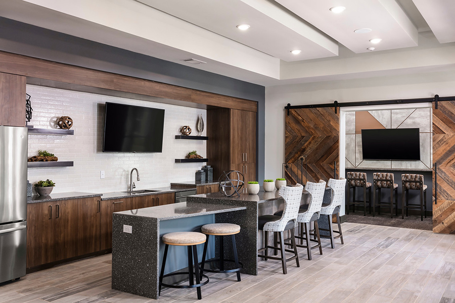 Lounge kitchen with tile floors, built in stone island with stools, stainless steel appliances, and large TV.