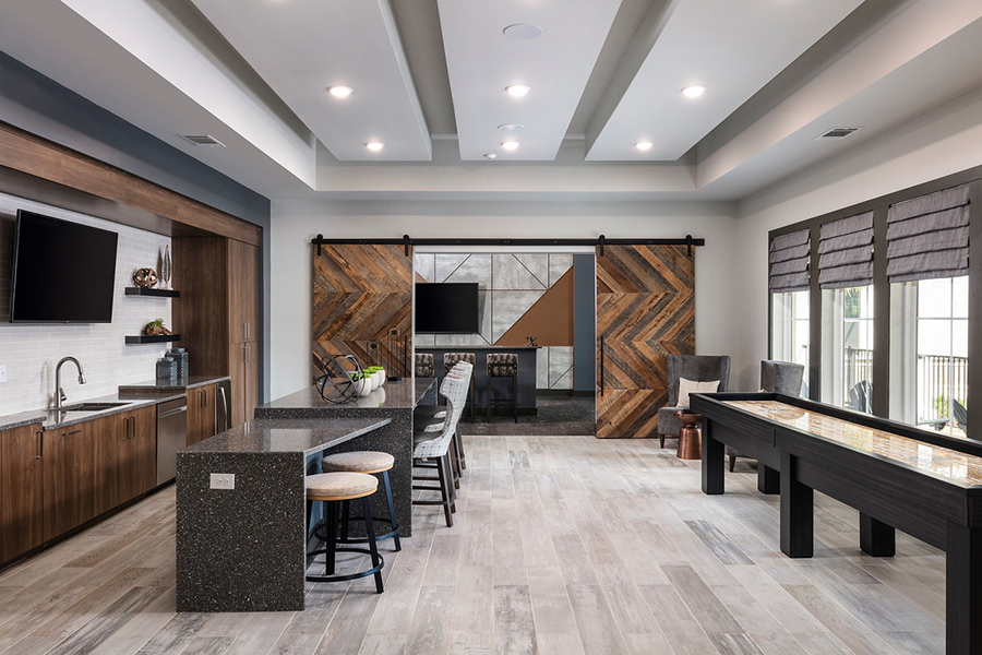 Lounge kitchen and gaming room with tile floor, island with stools, stainless steel appliances, and shuffleboard table.