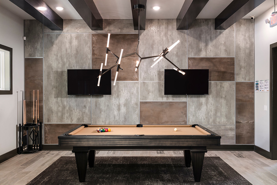Game room with tile floor, large pool table with cue rack, two wall mounted TVs, and modern lighting fixture.