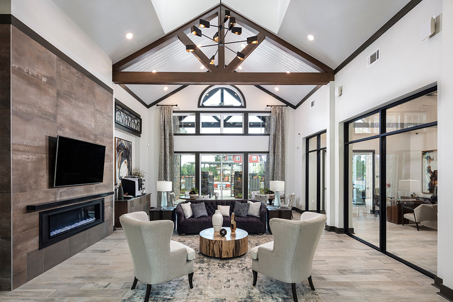 Clubhouse with tile floor, large fireplace with TV, comfortable furniture, and exposed ceiling beams.