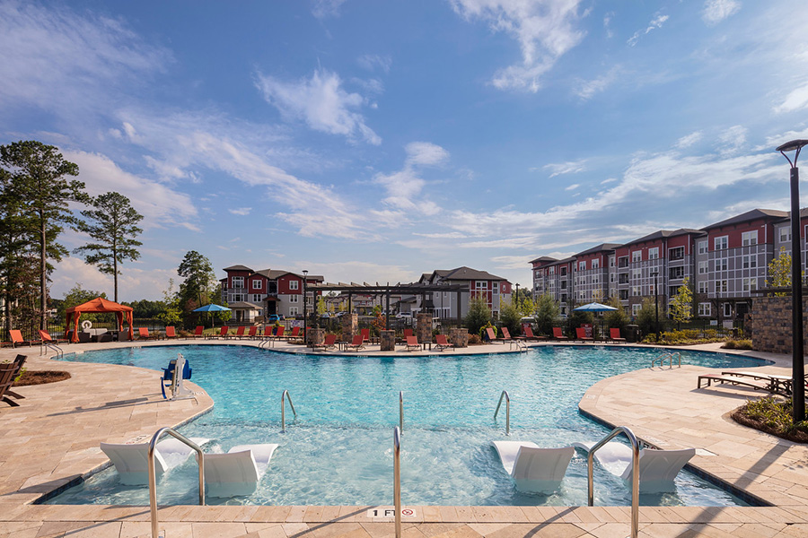 Pool area with stone paver patio, in pool lounge chairs, and pergola overlooked by apartments.