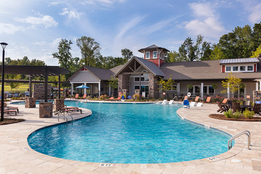 Pool area with stone paver patio, lounge chairs, pergola, and clubhouse.