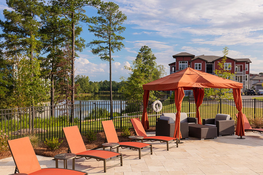 Pool area with stone paver patio, lounge chairs, gazebo, and tall trees in front of lake.
