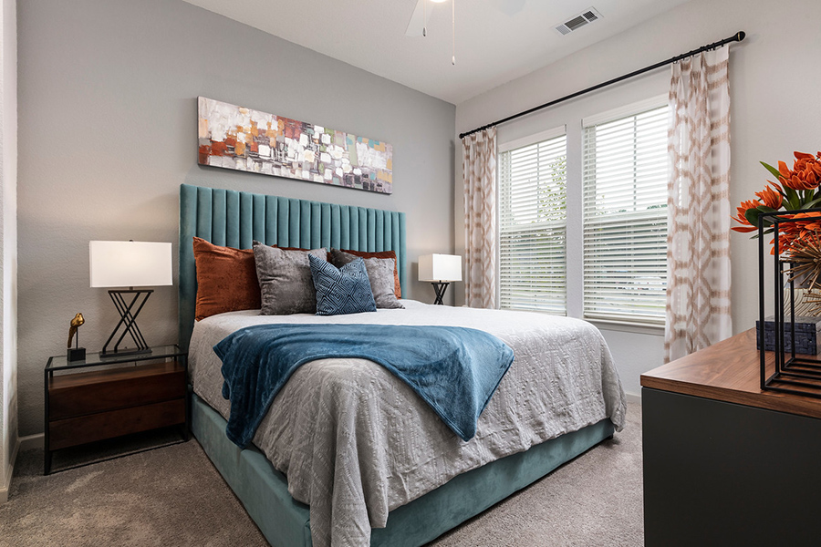 Bedroom with carpet floor, platform bed with plush bedding, bedside tables with lamps, and large windows.