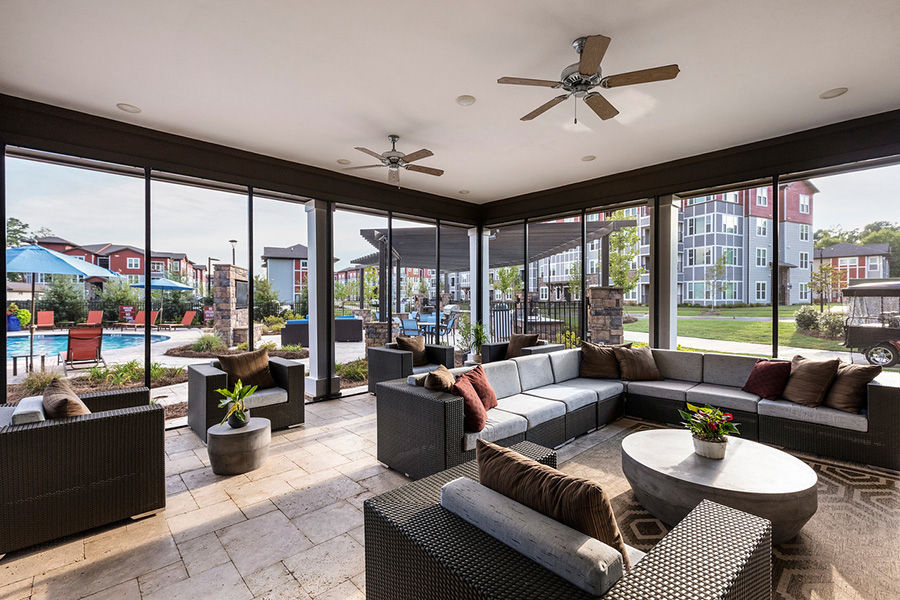 Lounge with stone paver patio, large outdoor sectional, ceiling fans, and large windows overlooking pool.