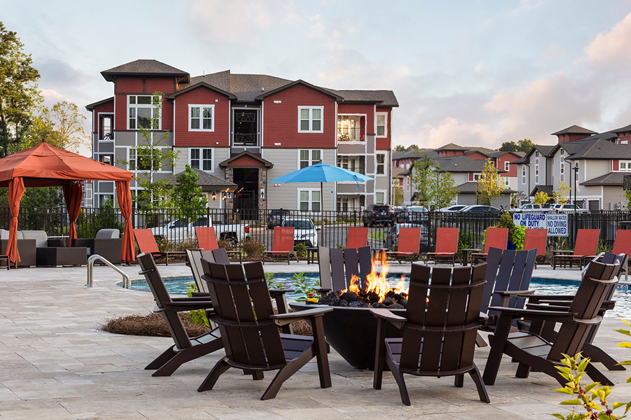 Pool area with stone paver patio, lounge chairs, firepit, and gazebo overlooked by apartment balconies.