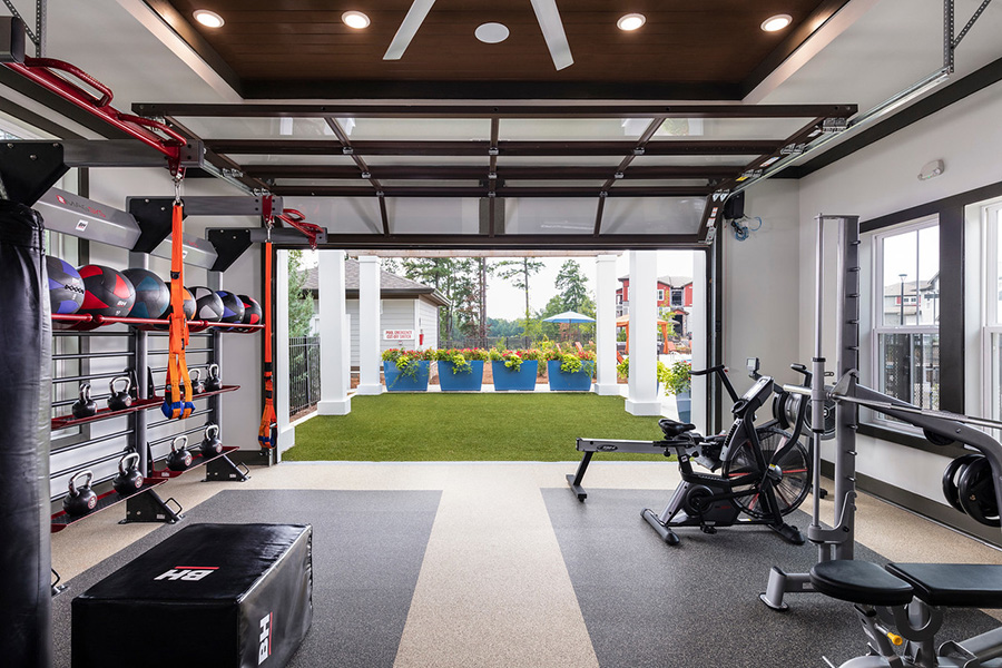 Fitness center with rows of cardio and weight machines, large ceiling fans, and garage door to outside.