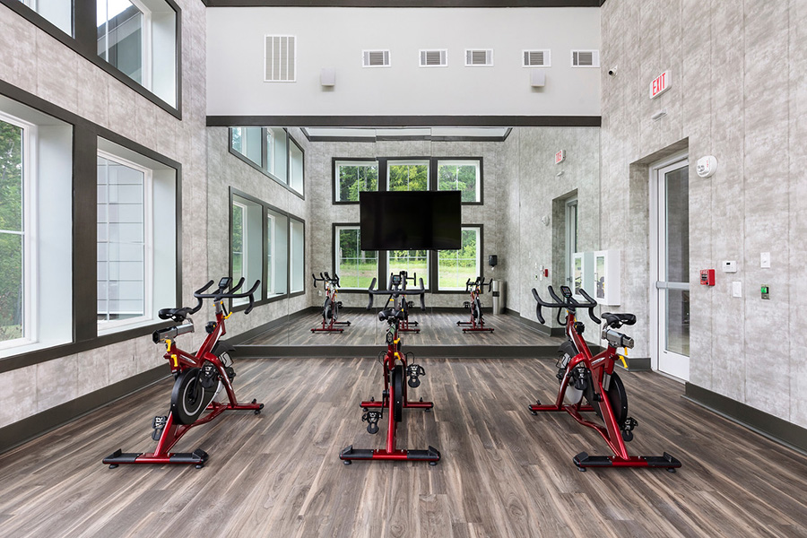 Spin room with wood floors, mirror wall with TV, and spin bikes.