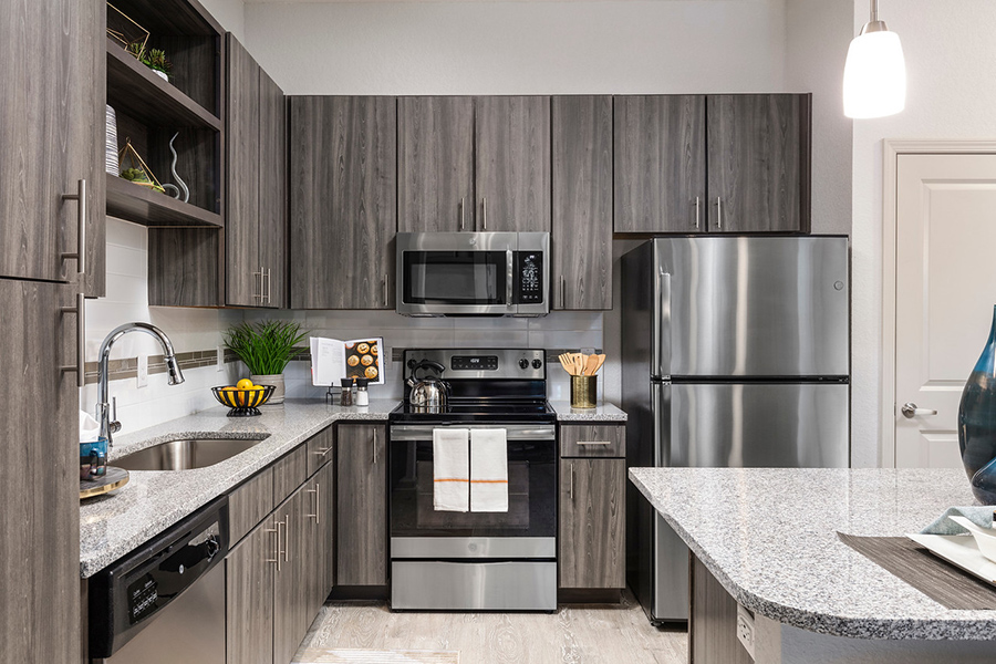 Kitchen with wood style floors and cabinets, stone counters, and stainless steel appliances.