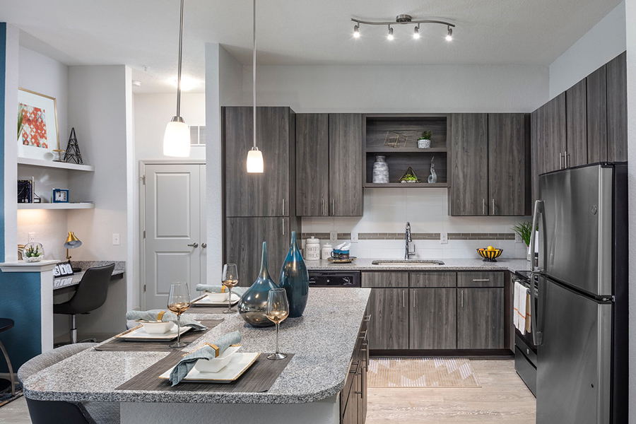 Kitchen with wood style floor, wood cabinets, stone counters, stainless steel appliances, and built in desk.