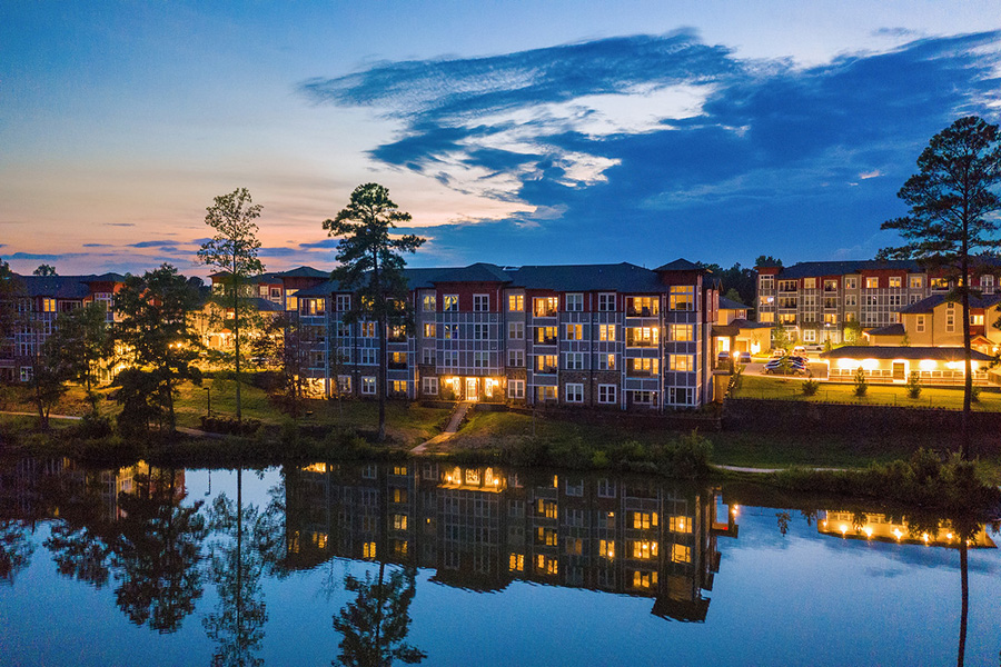IMT Edgewater apartments in evening with bright lights reflecting in lake.