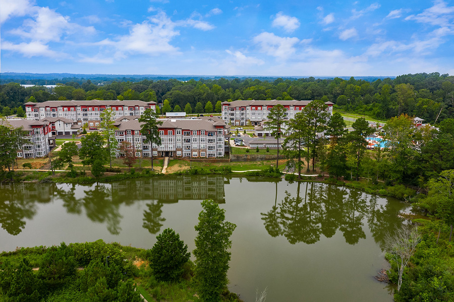 Aerial view of IMT Edgewater apartments near lake with tall trees and blue skies.