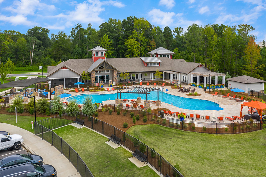 Clubhouse and pool area with pergola, lounge chairs, dog park, and lush landscaping.