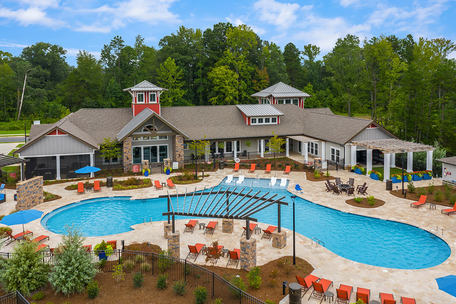 Clubhouse and pool area with pergola, lounge chairs, and lush landscaping.