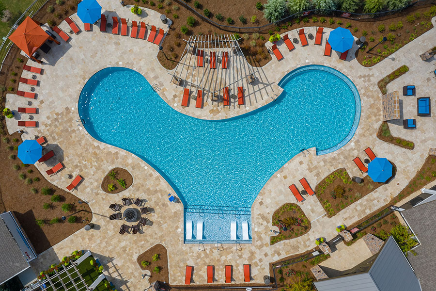 Aerial view of IMT Edgewater pool area with stone paver patio, lounge chairs, and landscaping.