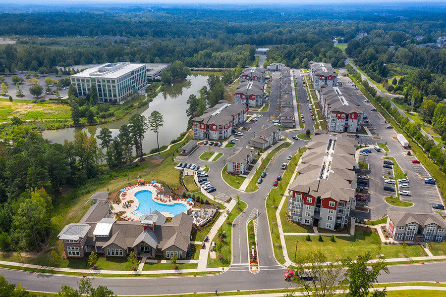 Aerial view of IMT Edgewater apartments with clubhouse, pool area, and ample parking.