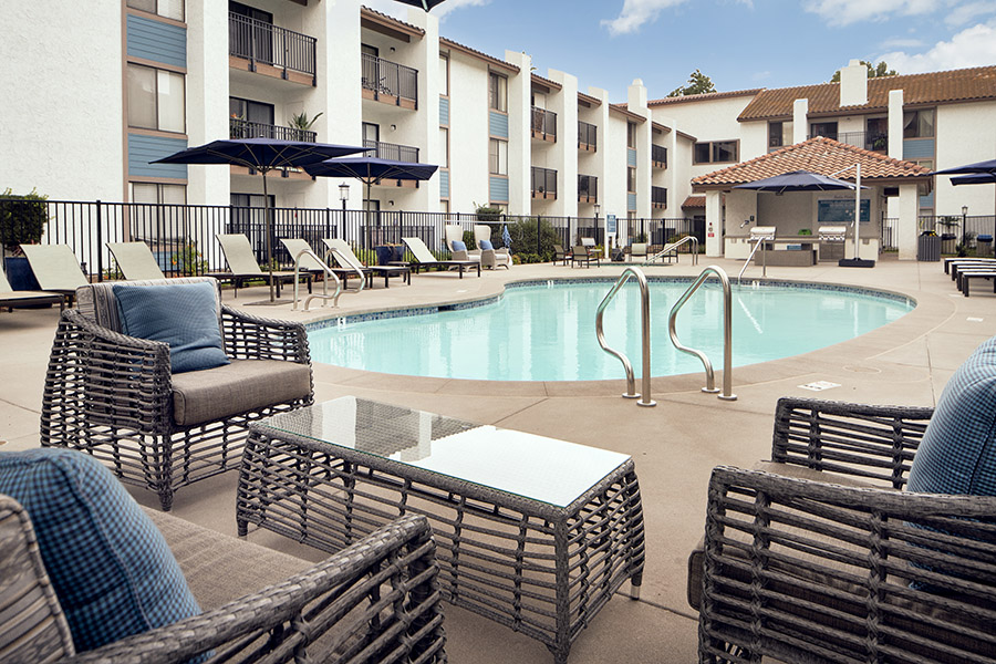 Pool with wicker furniture, lounge chairs, and built in BBQs overlooked by apartment balconies.