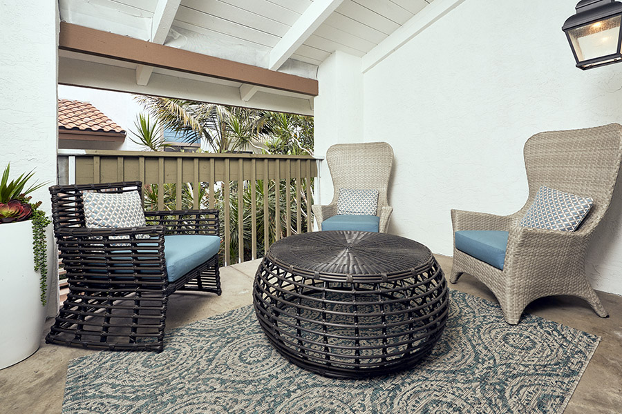Balcony with large rug, round wicker table, and wicker chairs overlooking palm trees.