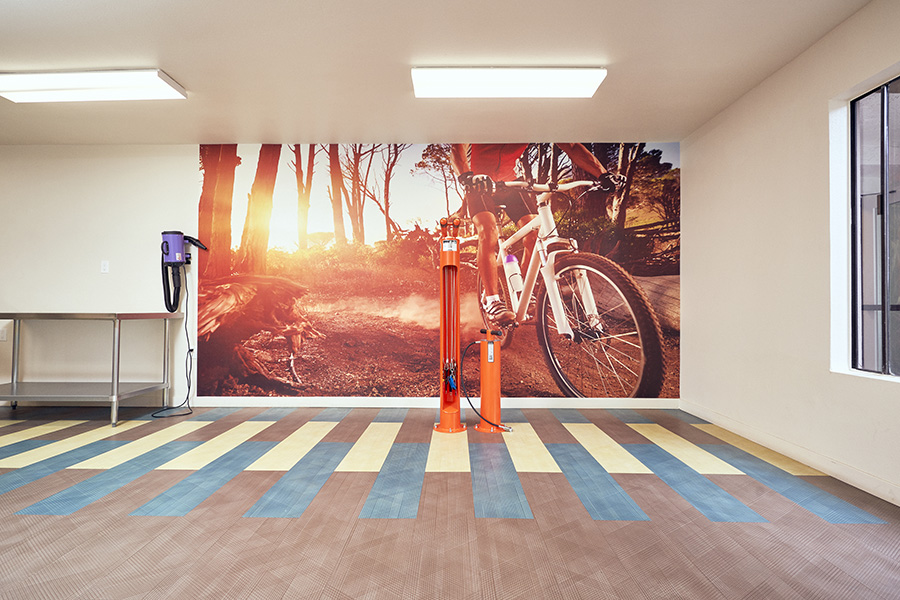 Room with large biking wall graphic and bike tire pump station.