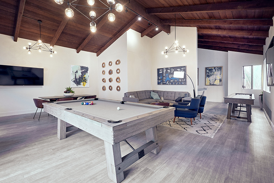 Lounge with wood floor, plush seating, games tables, and wood beams with geometric chandeliers.