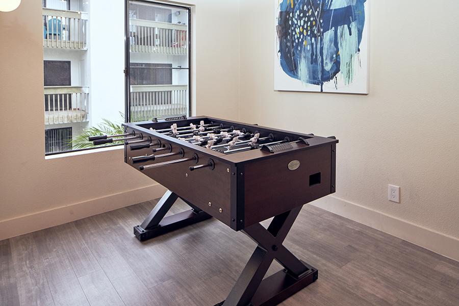 Game area with wood floor, wood foosball table and wall art.